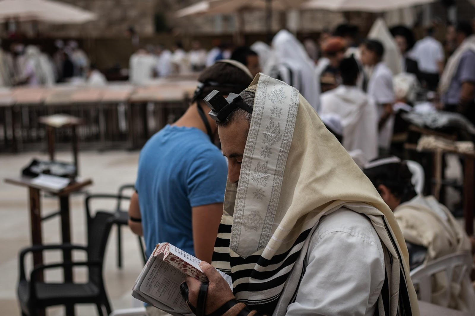 A Jew praying at the Western Wall, covered in Tallit wearing Tefillin