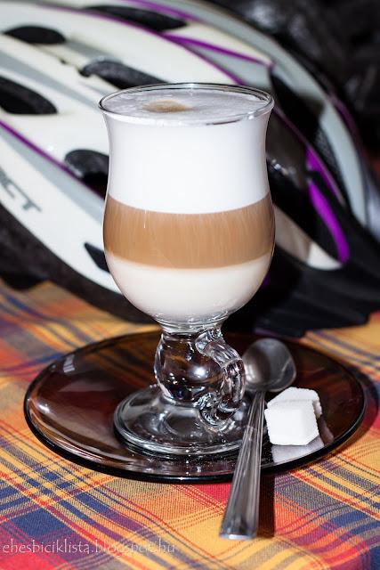 Cappuccino sok tejhabbal rétegesen és kockacukorral, háttérben biciklis sisak