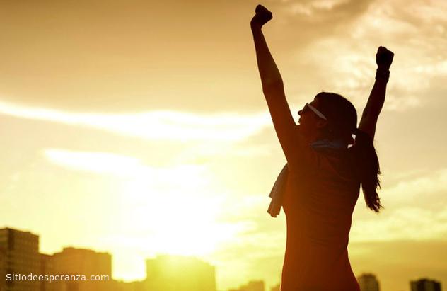 Mujer feliz levantando las manos al cielo