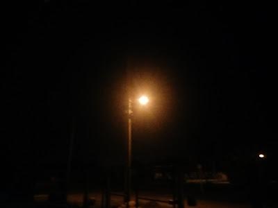 A foto mostra a iluminação na rua antes do temporal a noite.