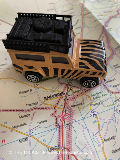 A beige and black painted toy Land Rover on a paper map next to the words Gabarone.