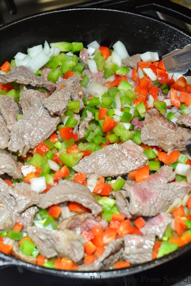 Partially cooked sliced steak with diced onion, diced red bell pepper, and green bell pepper in a cast iron pan.