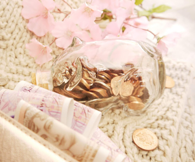 A glass piggy bank with a cork nose, filled with small change. There are pink flowers in the background behind it.