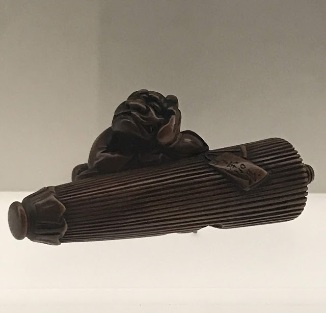 Photo of Ryukei wooden netsuke of a demon sleeping on an umbrella