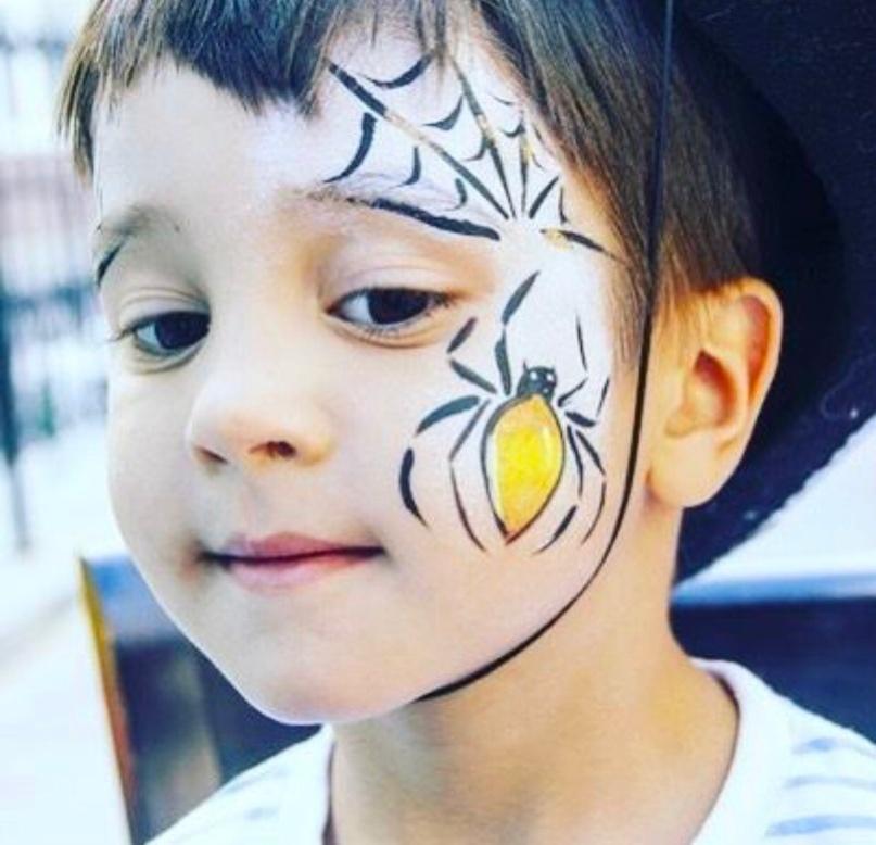 Maquillaje infantil telaraña y araña en mejilla y sien