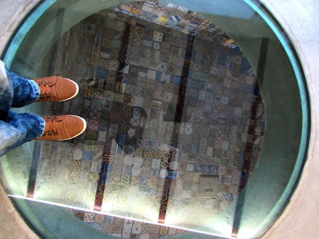 pés sobre um tampo de vidro que dá acesso à um cisterna revestida de azulejos