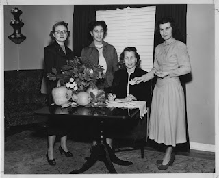Four women posing behind a table which is decorated with fall ornaments and pumpkins