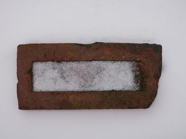 Broken brick in undisturbed snow framing rectangle of snow which has landed on it.