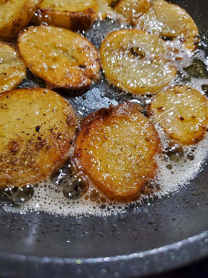 these are thin sliced potatoes frying to be made into salt and vinegar potato chips