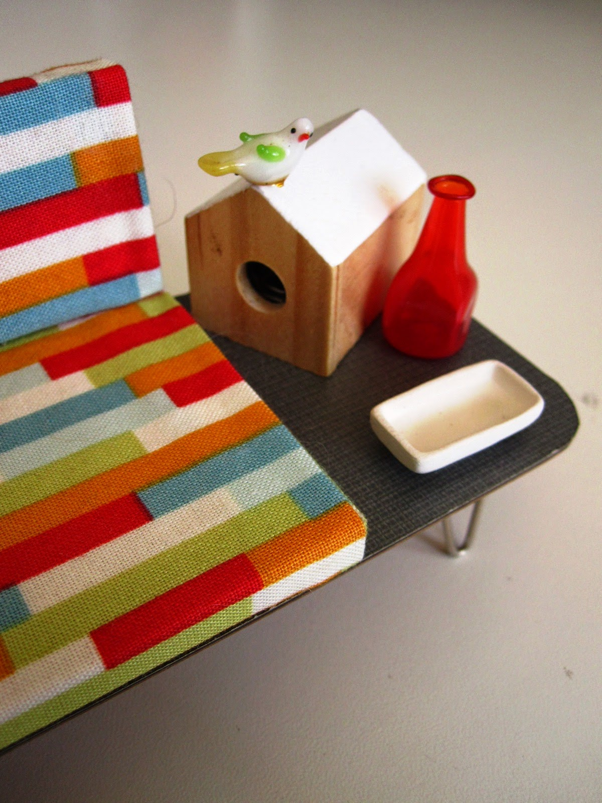 Mid century modern miniature sofa with attached coffee table, displaying mid century accessories including a bird house, bird, bottle and dish.