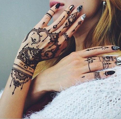 Muchacha rubia de cabello largo, se toca la cara con delicadeza, lleva tatuajes de henna en las manos