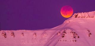 """Foto da """"superlua azul de sangue com eclipse"""" vista de Longyearbyen, na Svalbard(Noruega).  A mais """"completa"""" Superlua das últimas décadas aconteceu na manhã desta quarta-feira 31 de janeiro de 2018. Os moradores da parte oeste dos Estados Unidos e de regiões da Ásia e da Oceania acompanharam a Lua em sua versão mais brilhante – no ponto mais perto da órbita ao redor da Terra – e ainda com um eclipse total. Como era a segunda lua cheia no mesmo mês, ela recebeu o apelido de Lua Azul. Mas, na verdade, com o eclipse ela adquiriu uma cor avermelhada, a chamada Lua de sangue, uma consequência da sombra feita pela Terra. A Lua ficou completamente encoberta pela sombra da Terra no auge do eclipse. A super Lua azul de sangue com eclipse total é a combinação de quatro fenômenos: o primeiro: o eclipse em si; o segundo: quando a lua se aproxima da Terra e fica maior e mais brilhante; o terceiro: quando temos duas luas cheias no mesmo mês; o quarto: a Lua de sangue quando a sombra da Terra deixa uma tonalidade avermelhada na lua.  Descrição: Foto. A imagem divide-se horizontalmente. Acima, o céu totalmente arroxeado, abaixo, a montanha rosada e nevada. À direita, a montanha eleva-se em um pico e logo acima, a Lua, uma grandiosa esfera. Uma mancha roxa envolve a superfície superior da lua, esfumaça e encobre quase toda a lua em dégradée vermelho alaranjado, esmaece e descortina o amarelo vibrante na superfície inferior."""