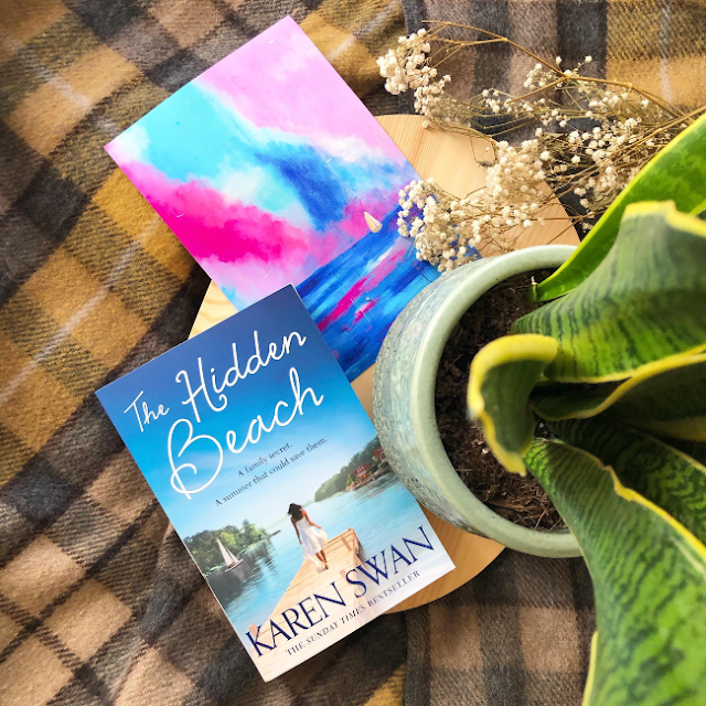 Cover of 'The Hidden Beach' by Karen Swan next to a print of a painting of a boat under a blue and pink sunset
