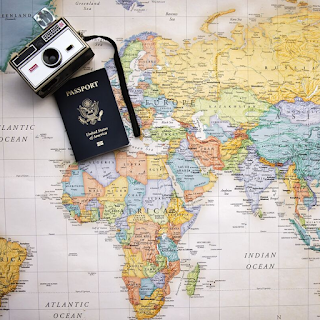 a passport and camera on the map of the world