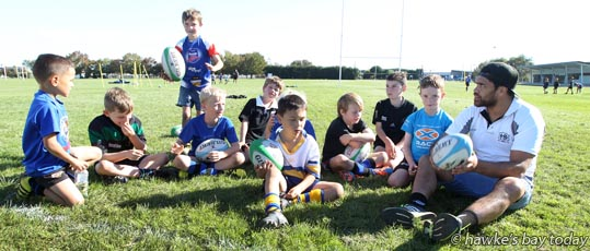 Right: Lewis Marshall, Hawke's Bay Magpies work with Hastings kids at a holiday event at Elwood Park, Hastings. photograph