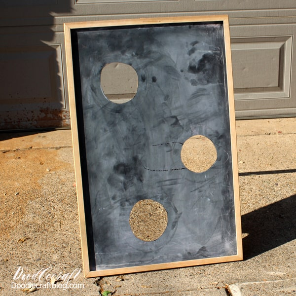 Holes cut in an old chalkboard for a bean bag toss game