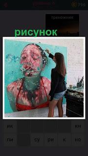 девушка на стене рисует картину девушки в купальнике под водой