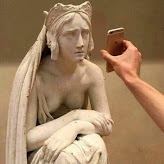 A statue peering at a cell phone held up before her face