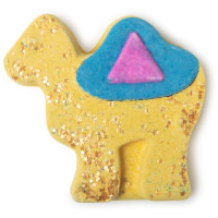 A light green-yellow camel shaped bath bomb with a bright blue saddle on top on a bright background