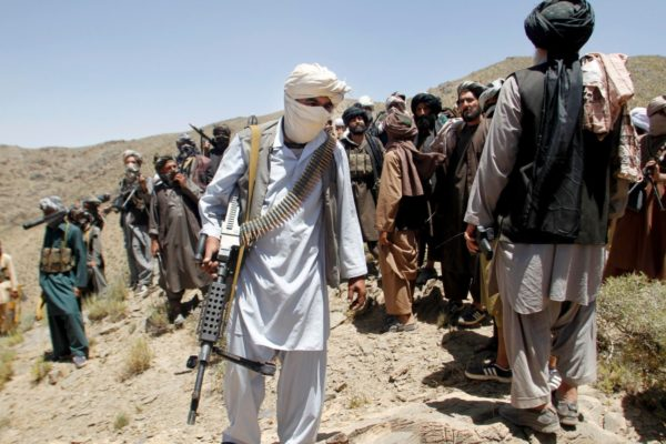 Taliban fighters: overrun Afghan policeman