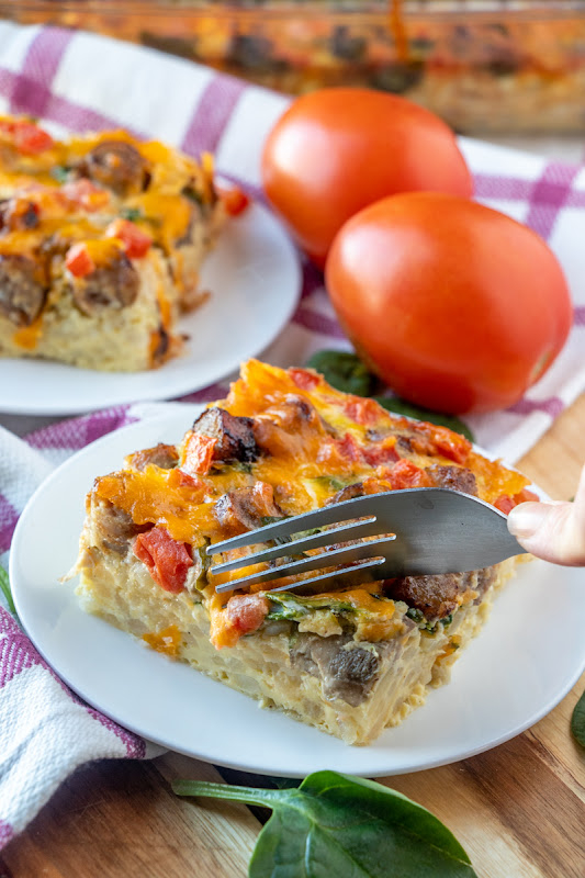 This breakfast casserole is great for Sunday morning breakfast, brunch or serve for the holidays! Tons of flavor from cheese, sausage, mushrooms, spinach, tomatoes, hash browns and onion. Simple to make and enough to feed the whole family!
