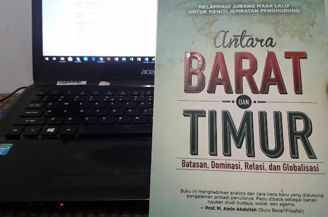 sebuah buku dengan latar belakang laptop penulis