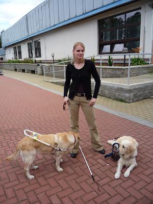 Linda stojí před hotelem. U nohou leží zlatý retrívr a vedle stojí světlý labrador v postroji