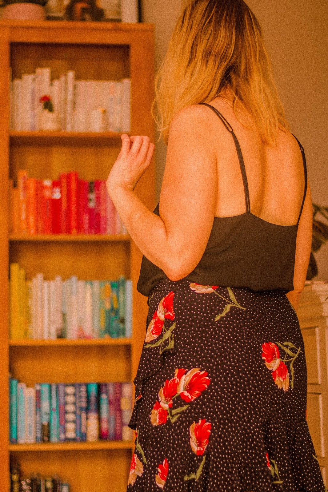 blonde girl looking at bookshelf