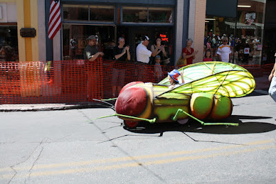 A child in a red, white & blue hat in an green insect-shaped vehicle. People are standing on the curb in the background.