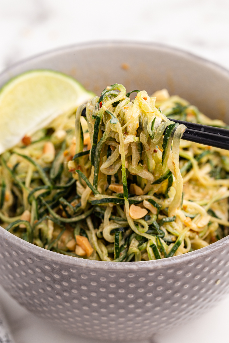 Close up photo of Spicy Peanut Cucumber Noodle Salad in a gray bowl with a bite on chop sticks.
