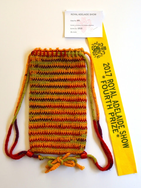 "A striped, rectangular drawstring bag is laid flat next to a yellow ribbon ""2017 Royal Adelaide show *Fourth Prize*"" with the Royal Agricultural Society's coat of arms. The exhibitor card is attached to the top of the ribbon."