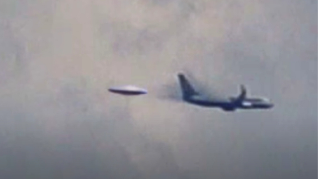Flying Saucer darts out of the clouds and nearly hits a large airplane.
