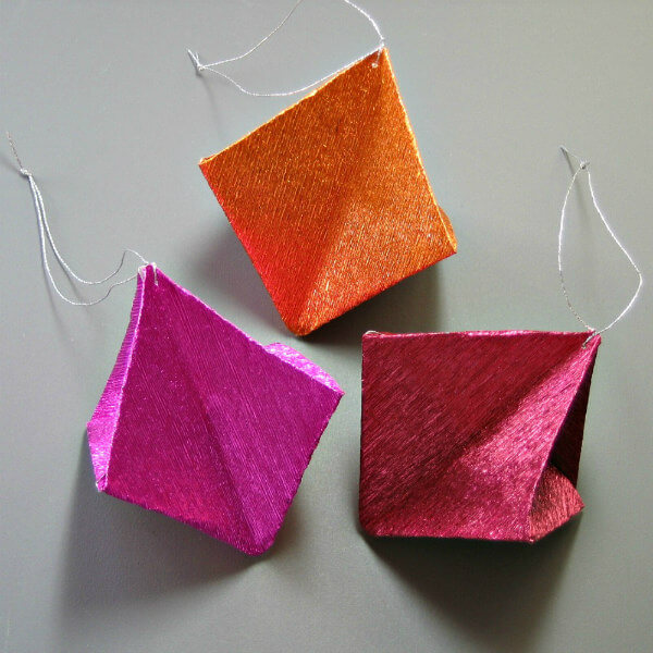three metallic crepe paper origami ornaments, red, orange, fuchsia