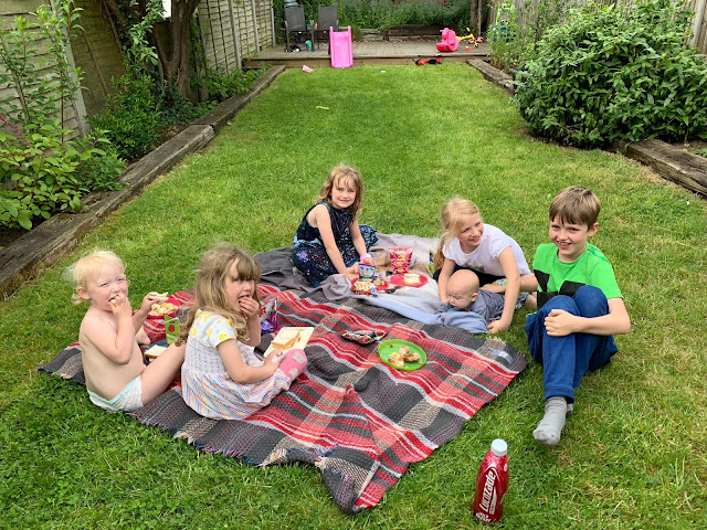 7 children ranging from 0 to 10 having a picnic in the garden on picnic blankets