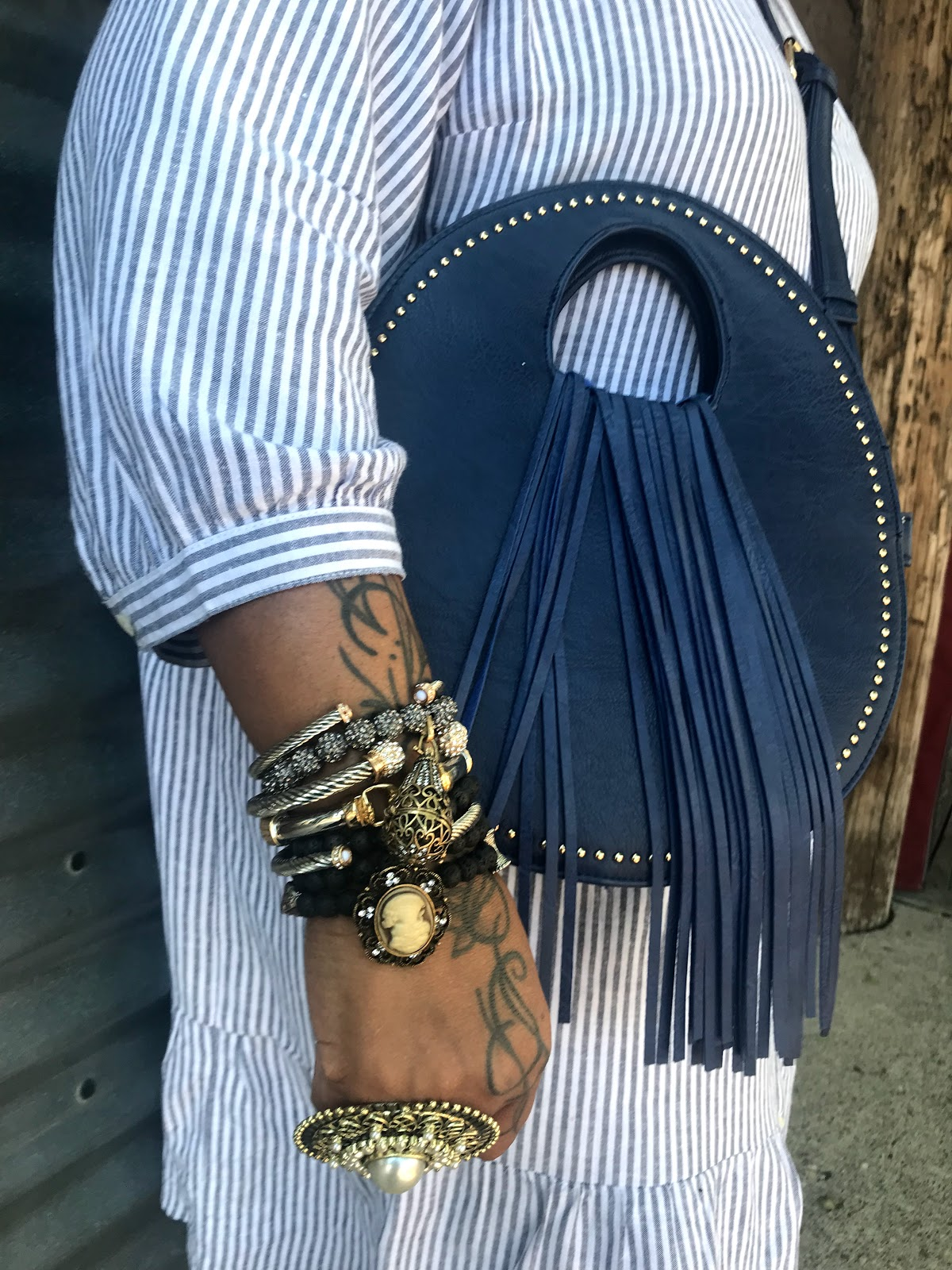 Image: Woman leaning on wall and sharing her story about midlife to motivate others. Tangie Bell is wearing a gold ring, arm bracelets, blue purse with tassels, and a blue and white stripe dress. Seen first on Bits and Babbles blog