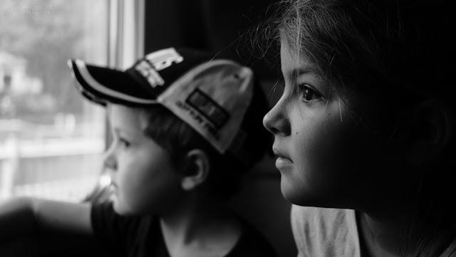 Volti di bimbi che guardano dal finestrino del treno