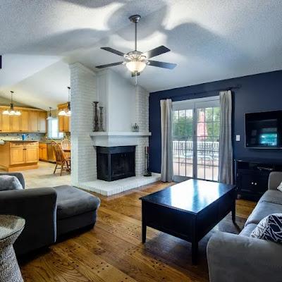 Foto imagem de um living com sofás escuros e lareira em tijolos pintados de branco, parede azul marinho, piso em madeira natural com uma mesa de centro e ao fundo uma cozinha com armários em madeira clara e uma ilha.