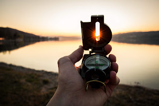Hand with a compass, directed to the sun, sunset