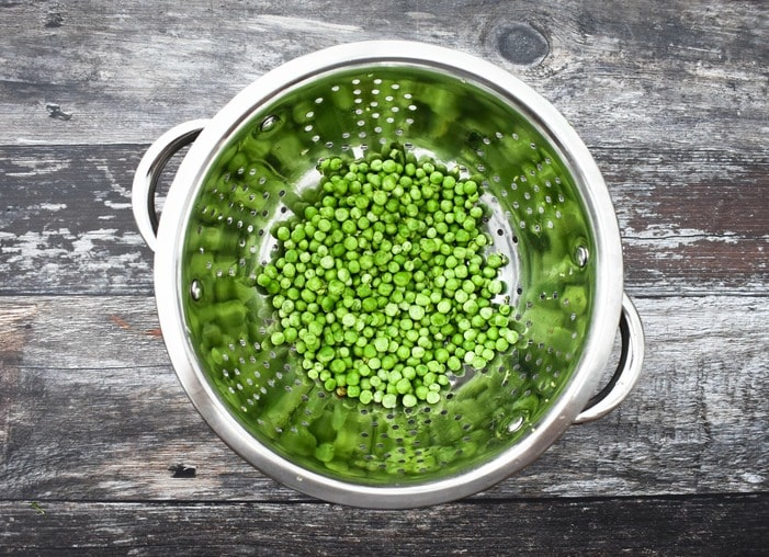 frozen peas in a colander