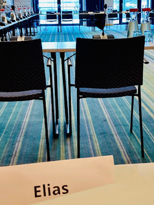 Tische zum Quadrat, Stühle zum Quadrat, blauer Teppichboden und zwei Dolmetscherinnen