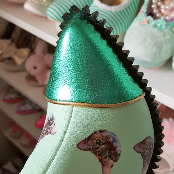 green metallic pointed toe of boot with spiked edging