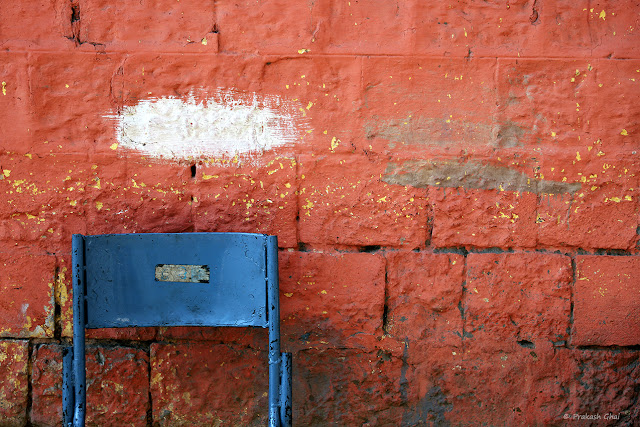 A Minimal Art Photograph of a patch of White Paint above a Blue Chair, on an Orange Wall.
