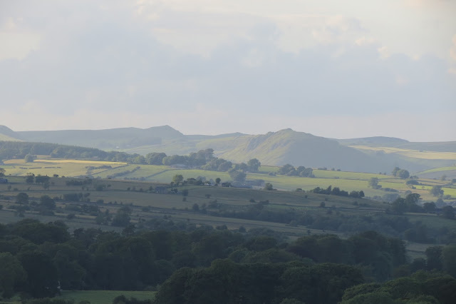 In the distance across farmland, the distinctive ridges of two Derbyshire hills.