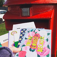 A red postbox with a colourful array or envelopes and postcards being held up ready to be posted.