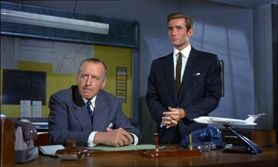 Cecil Parker sitting at a desk with Jim Dale standing alongside