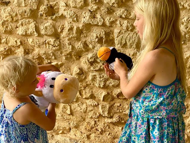 2 girls playing with unicorn and penguin FlipaZoo plushes