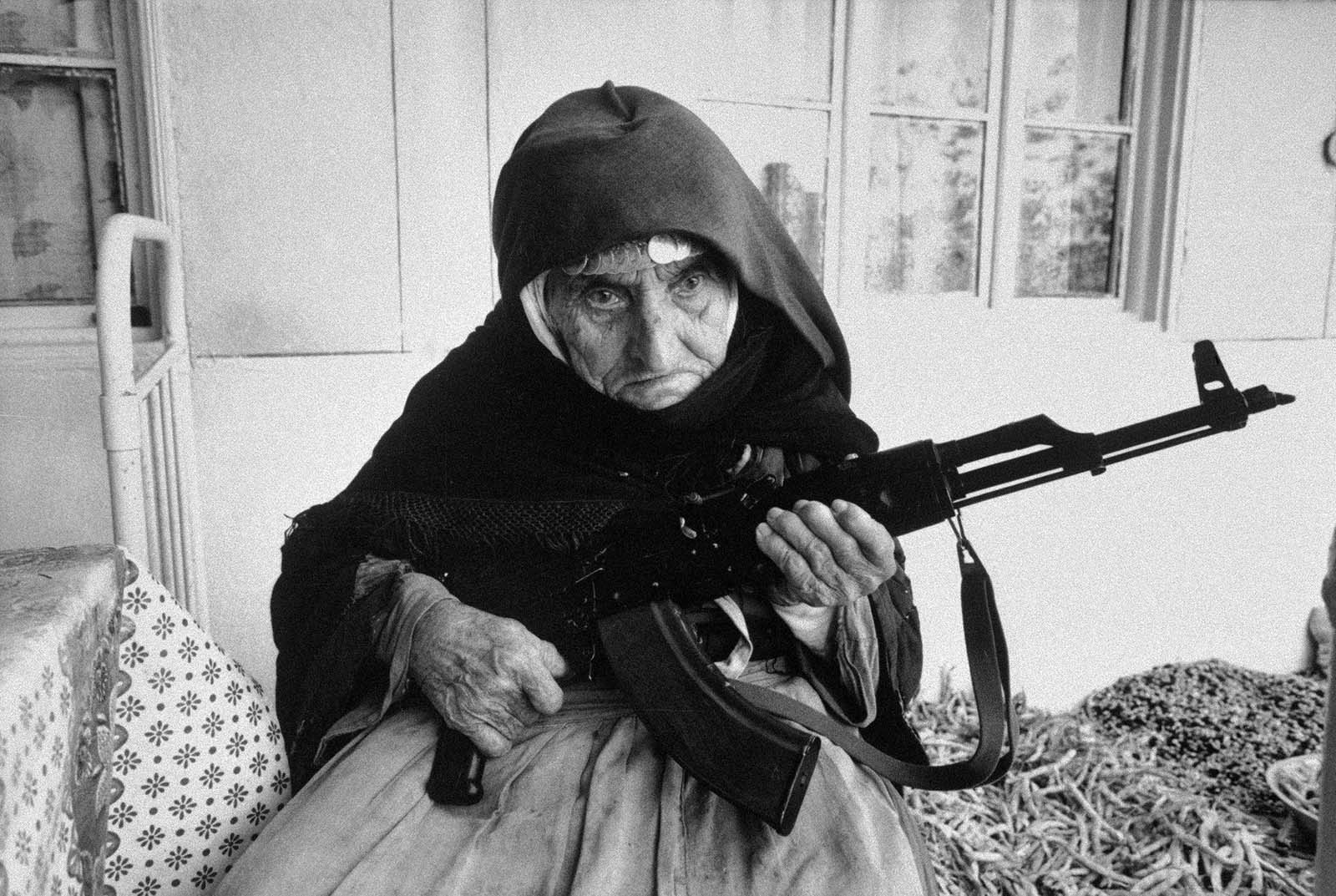 A 106-year old Armenian woman protecting her home with an AKM, 1990.