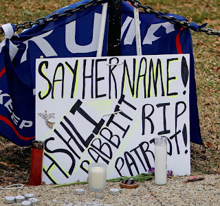 """Sign: """"Say her name! Ashli Babbitt, RIP Patriot?"""" with memorial candles in front"""