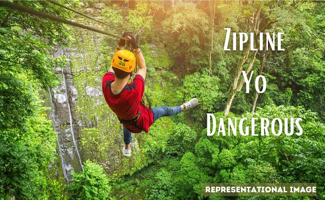 man slithering through a zipline at a tourist spot