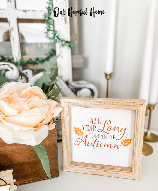 faux fall floral arrangement on mantel with small wooden fall sign